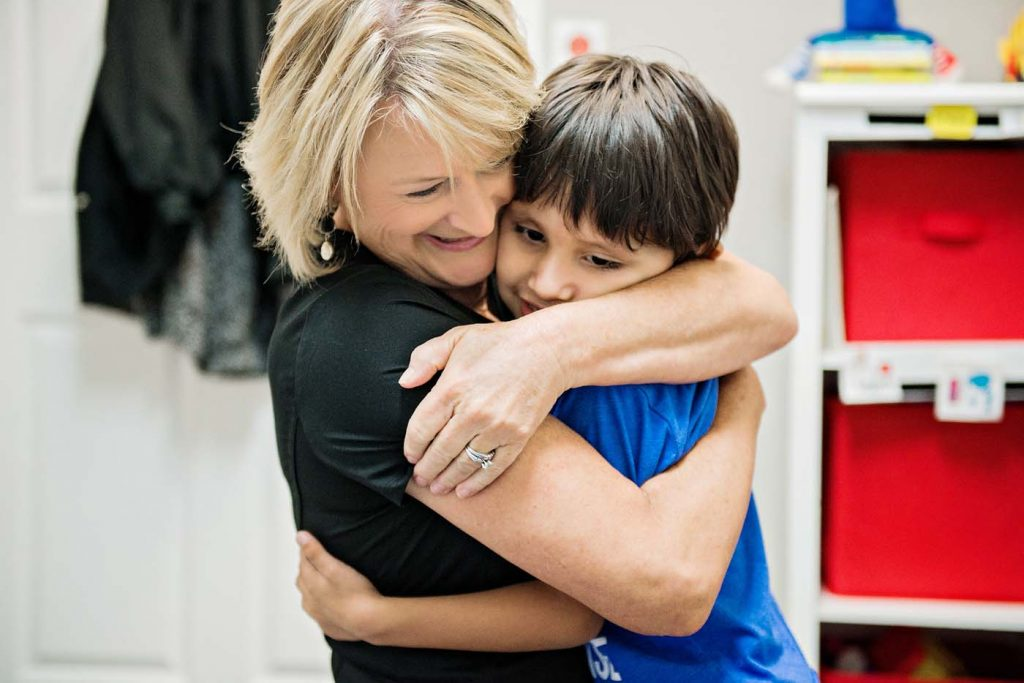 Therapist hugging cut kid