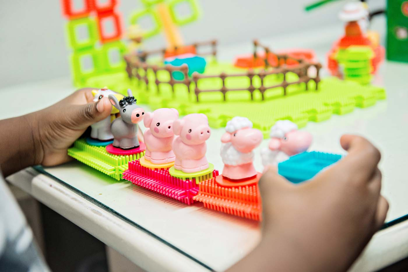 child's hands with farm animal toy
