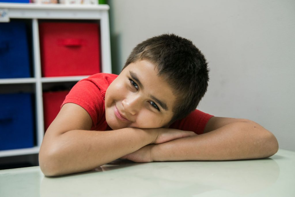 Boy smiling laying head on the table